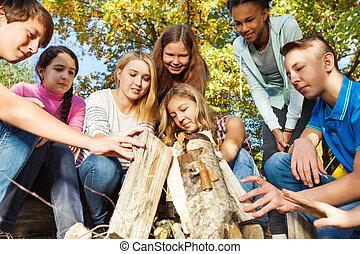 International teens construct bonfire together