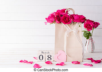 International Womens day concept. Pink roses in paper bag with March 8 text on wooden block calendar on white wooden background.