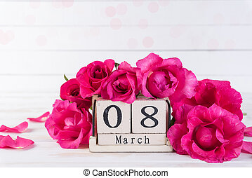 International Womens day concept. Pink roses with March 8 text on wooden block calendar on white wooden background.