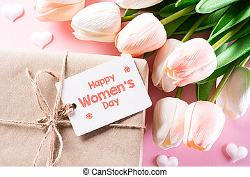 International Women's Day concept. Woman present, pink and white tulips with paper tag text on bright pink pastel background. flat lay, March 8.