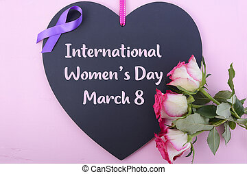 International Womens Day, March 8, heart shaped blackboard greeting with purple ribbon symbol and pink roses on pink wood background.