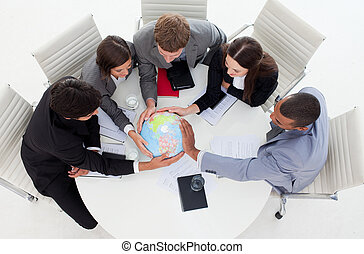 Internatonal Business team holding a terrestrial globe in a ...