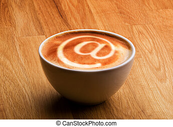 Internet Cafe Concept - A cappuccino with an @ sybol in the...