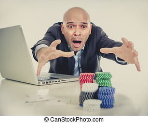 internet gambling addict businessman on computer loosing lots of money betting on poker game