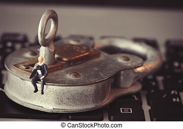 Internet security concept-miniature businessman stand on old key and padlock on laptop computer keyboard