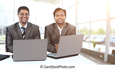 Interracial business team working at laptop in modern office