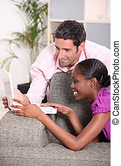 Interracial couple looking at a laptop.