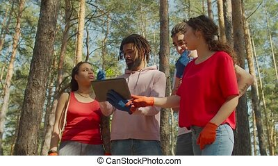 Positive chatting interracial diverse eco volunteer team planning and discussing work for cleaning forest rubbish using tablet pc, caring for purity of nature and environmental conservation.