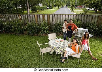 Interracial family having back yard barbecue - Interracial...