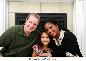 Interracial Family - Interracial family sitting together at...