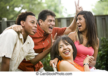 Interracial family making silly gestures posing for ...