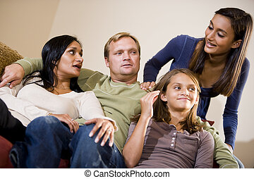 Interracial family of four sitting together on living room sofa