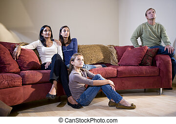 Interracial family sitting on living room couch watching TV