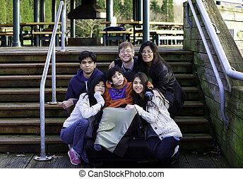 Interracial family surrounding disabled boy in wheelchair outdoo
