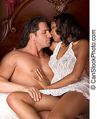 Interracial heterosexual sensual couple in bed