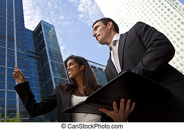 A smiling Indian Asian businesswoman and her male colleague taking part in a happy business meeting outside in a modern city environment