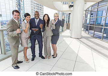 Interracial business team, men & women, businessmen & businesswomen, using tablet computer or iPad and celebrating successs on a city rooftop