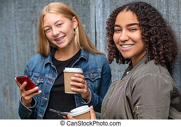 Interracial Mixed Race Girl Teenagers Using Smart Phones Drinking Coffee