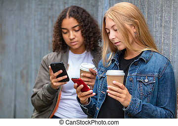 Interracial Mixed Race Girl Teenagers Using Smart Phones Drinking Coffee