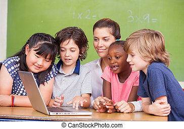Interracial primary classroom learning to use laptop with their