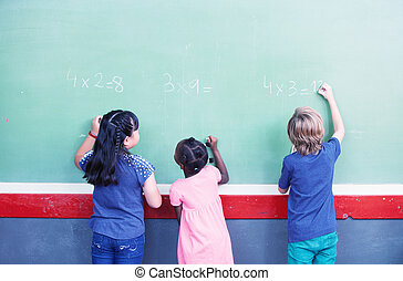 Interracial students writing numbers on chalkboard at elementary