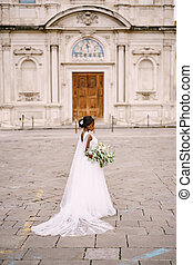 Interracial wedding couple. Wedding in Florence, Italy. African-American bride in a white dress with a bouquet in her hands, with a long veil stands on the street, against the background of the church