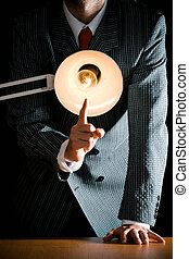 Suggestive interrogation concept - interrogating person standing behind desk lamp