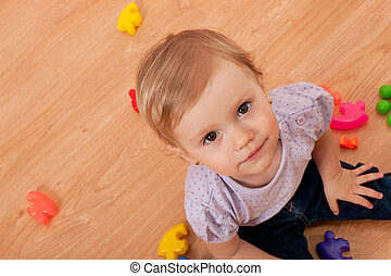 A little girl sitting on the floor is playing her toys