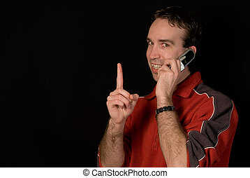 Interruption - A young man on his cellphone holding a finger...