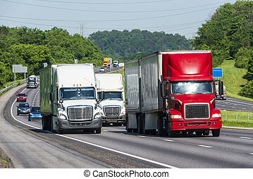 Tractor-trailer trucks lead traffic down the highway. Note: All logos and identifying marks have been removed from all vehicles. Image was created on hot day, so heat waves from the asphalt create some distortion, especially on vehicles farther from the camera, enhancing the long telephoto effect.