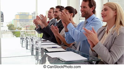 Interview panel applauding the applicant in the office
