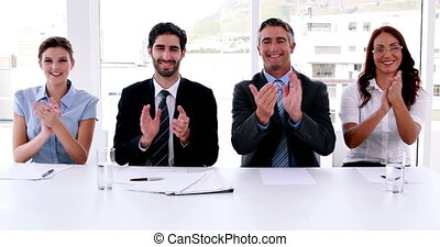 Interview panel applauding the camera in the office