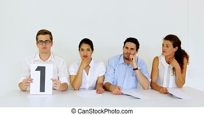 Interview panel holding up low scores in the office