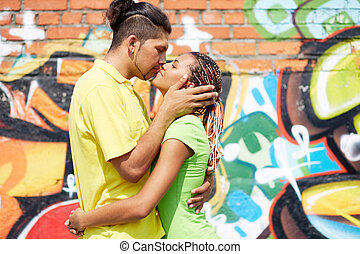 Image of young couple embracing on background of graffiti wall