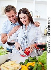Intimate couple drinking wine while cooking in the kitchen...