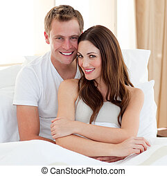 Intimate couple hugging lying in bed at home