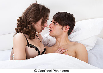 Intimate Couple Looking At Each Other In Bed