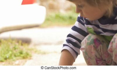 Intimate moment with a cute little girl focused on playing outside