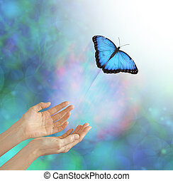 metaphorical representation of releasing or letting a soul go, into the light, using a butterfly, female hands and an ethereal background & white light