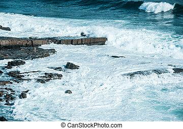 Breaking wave heading towards area of white water surging around coastal rocks at North point, Cowaramup Bay, Gracetown, Western Australia