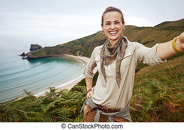 woman hiker taking selfie in front of ocean view landscape