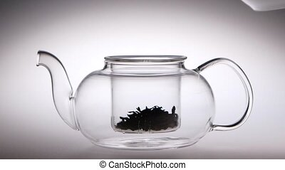 Into transparent teapot with tea leaves is poured boiling water