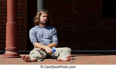 Intoxicated Man - Intoxicated young adult man sits barefoot...
