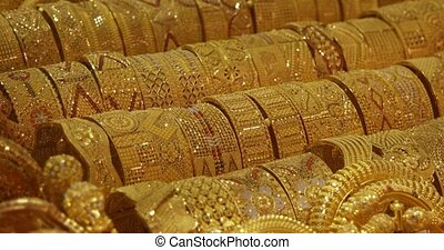 Many gold bracelets and other jewelry items with intricately detailed patterns, on display for sale in a Dubai public market.