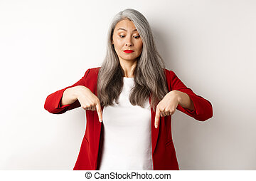 Intrigued asian elegant woman looking and pointing fingers down, showing logo, standing in red blazer over white background