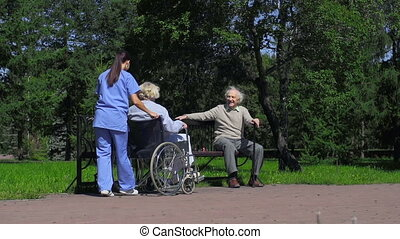 Young nurse introducing woman in wheelchair to man with stick