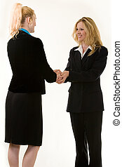 Two attractive blond business women warmly shaking hands both standing on white background