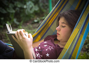 introvert teenager girl reading book in hammock