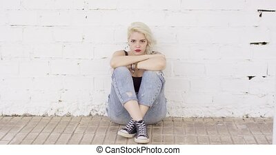 Introvert young woman sitting on paving thinking