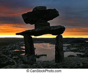 Inukshuk overlooking Newfoundland town - St Anthony area,...